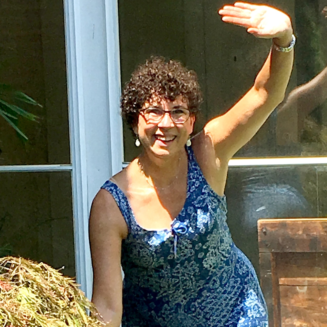 a curly-haired woman waves a greeting while watering the garden