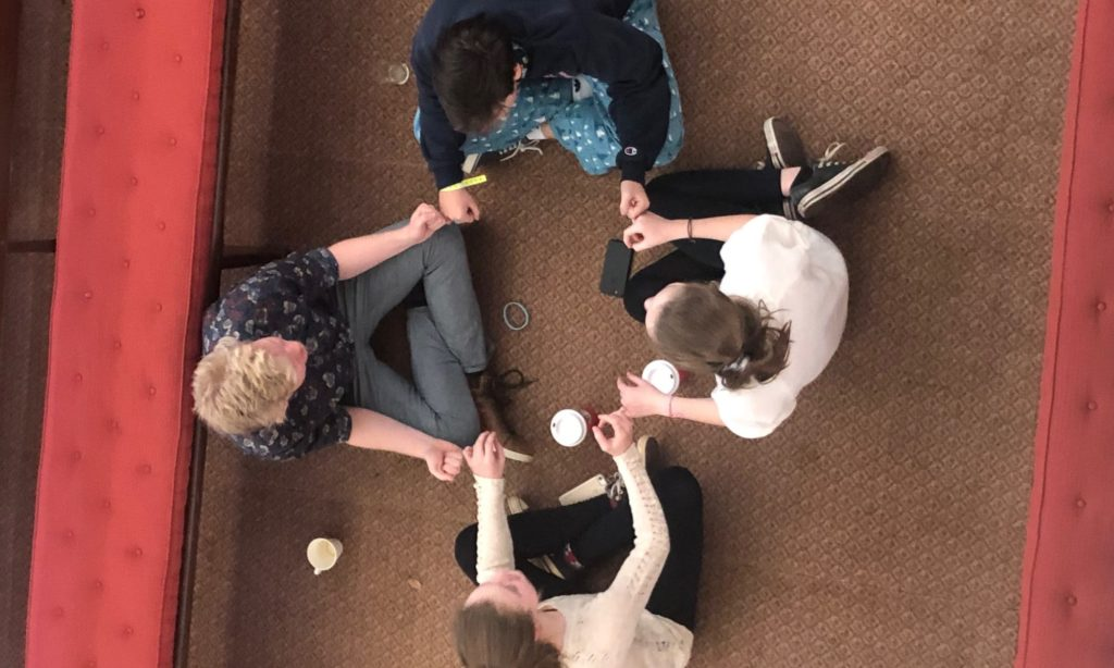 overhead view of four people sitting cross-legged in a circle