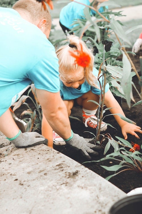 an adult and a child plant a flower