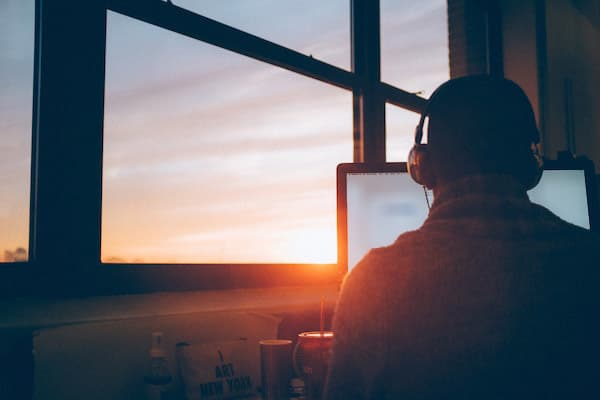 someone reading on the computer, wearing headphones and facing the dawn