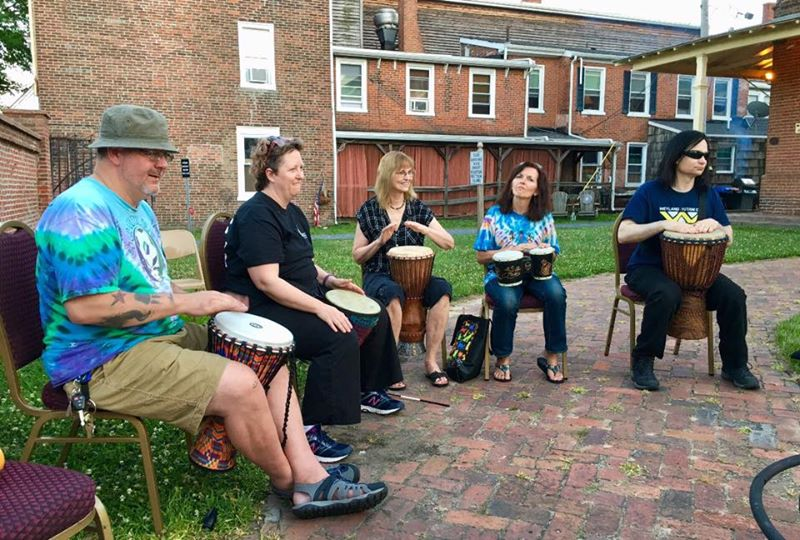 5 Quakers having a drum circle outside