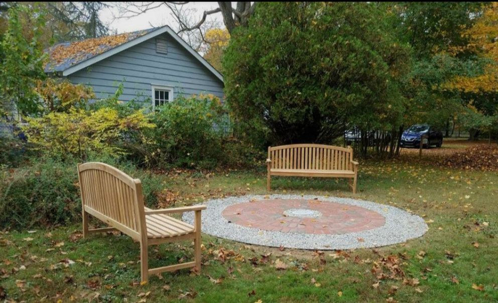 two teak benches sit either side of a circular patio