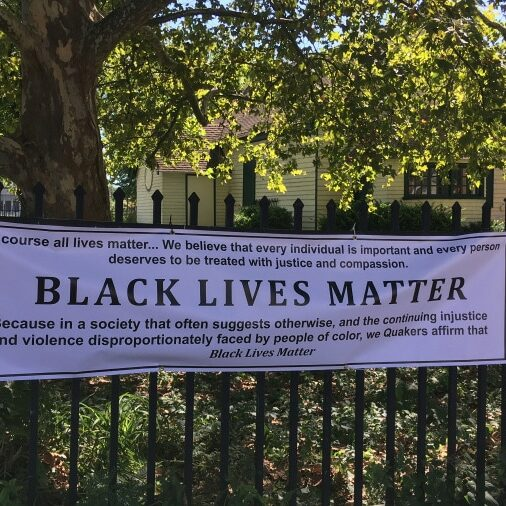 a Black Lives Manner banner hanging on the fence in front of a meetinghouse